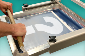 A picture of someone screen printing manually.